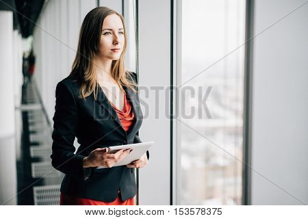 Young business woman in a red dress and jacket standing near the window with tablet gadget winter city landscape outside the window on the background
