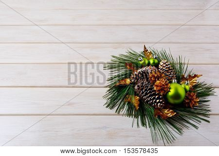 Christmas greeting with pine branches and golden cones. Christmas centerpiece with golden decor. Christmas party background. Copy space.