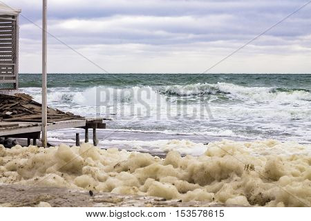 lot of sea foam and powerful sea splash wave with sprays and destructive effects of the storm on the coast