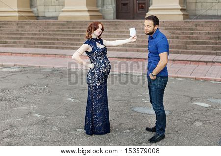 Funny image. Сouple expecting a baby: woman holds a sign with space for text