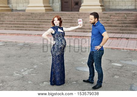 Funny image. Сouple expecting a baby girl: pregnant mother holds a sign saying