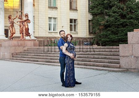 Pregnant red hair woman in long blue dress and stylish man embrace outdoor in city.