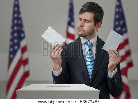 Undecided Voter Holds Envelopes In Hands Above Vote Ballot And M