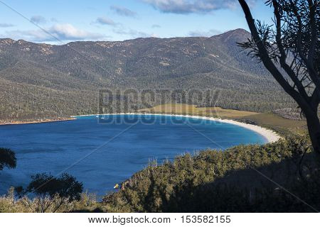 Tree-framed view overlooking the perfectly round beach at Wineglass Bay in Freycinet National Park Tasmania Australia