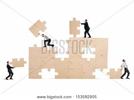 Team of businessmen collaborate and cooperate to build a puzzle