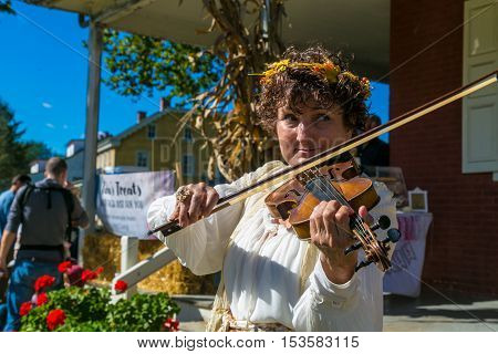 Lancaster PA USA - October 9 2016: A violinist entertains visitors at the Landis Valley Farm and Museum during the annual Harvest Day event.
