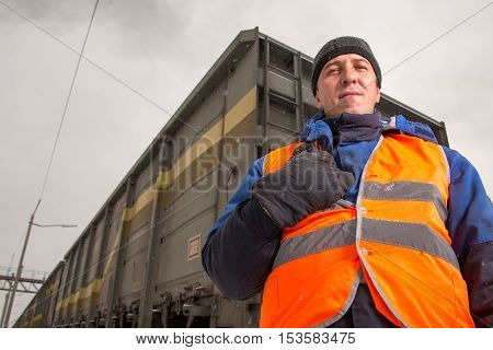 RUSSIA - OCTOBER 19: Rail worker coordinating cargo loading to transport train on the tracks