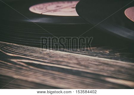 old vinyl record on the wooden table, selective focus and toned image