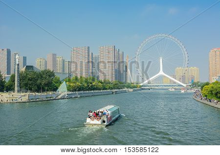 Tianjin,China - October 5,2016 : Cityscape of Tianjin ferris wheel,Tianjin eyes with tourist boat;selective focus at ferris wheel. Most modern popular landmark in Tianjin city China.