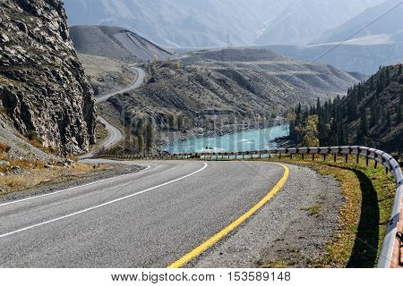 Scenic autumn view of the winding asphalt road along the river the mountains and the river with turquoise water