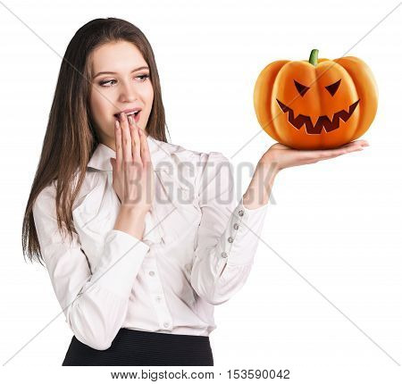 Surprised woman holding carved pumpkin isolated on white. Halloween concept