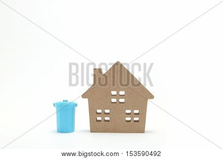 House and miniature blue plastic garbage bin on white background.