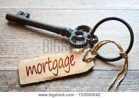 Old key with paper label - mortgage text - on wooden background. Real Estate Concept.