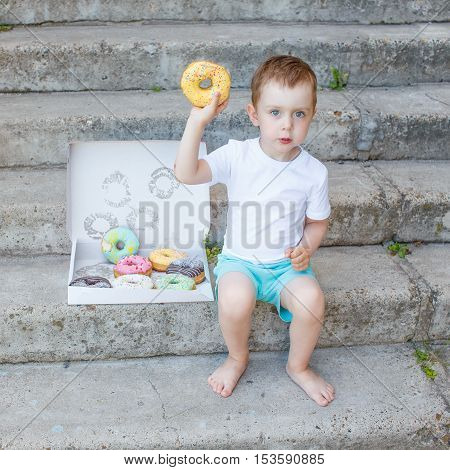 kid holding a donut. boy sitting on the steps with a box of colorful glazed donuts. little child playing with a donut. concept of junk food for kids
