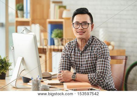 Portrait of Vietnamese cheerful web designer in glasses
