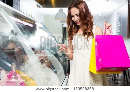 Stylish young female shopper making a selection of food from a glass counter in a deli standing holding up her colorful shopping bags with a happy smile