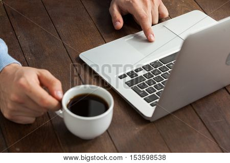 Man using laptop while having cup of coffee on wooden table