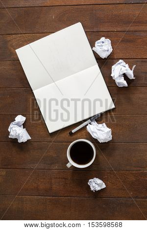 Notepad, pen, crumpled paper and cup of coffee on wooden table