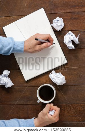 Man writing on notepad and crumpling paper while having cup of coffee
