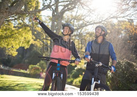 Biker couple with mountain bike pointing in distance on a sunny day