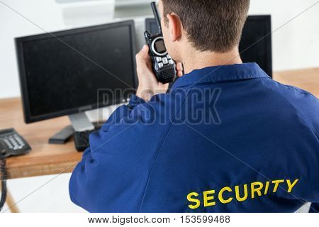 Rear view of security officer talking on walkie-talkie while looking at computer monitors