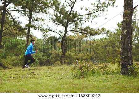 Side view of man jogging in morning forest