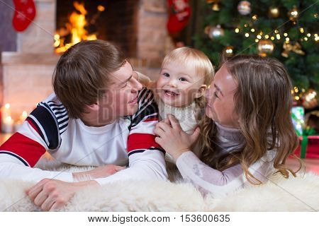 Happy family mother father and baby little boy playing in the winter for the Christmas holidays
