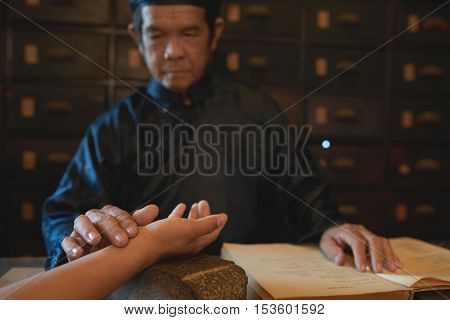 Senior Vietnamese man checking pulse of patient to define his disease
