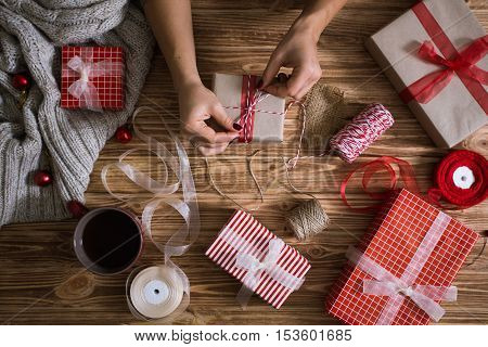 Female Hands Wrapping Christmas Presents In Paper And Tying Them With Red And White Threads