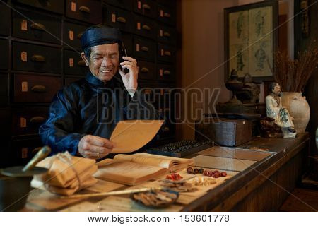 Senior Asian man taking on phone from apothecary