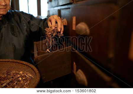 Hands of man taking herbs from the drawer