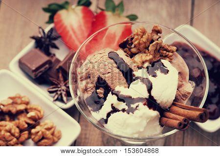 Ice cream sundae, chocolate, walnuts and sliced strawberry