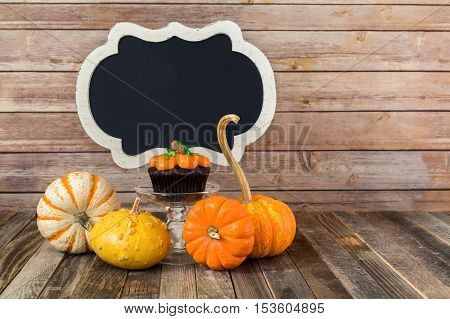 Fall pumpkin muffin with blank chalkboard sign and decorative gourds