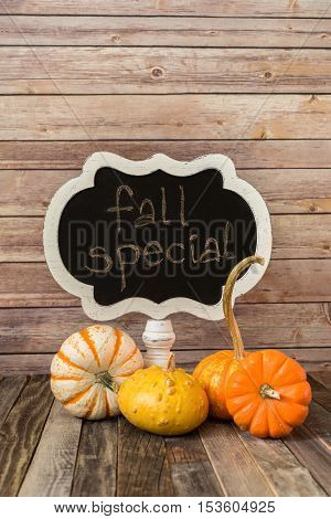 Chalkboard sign and four orange decorative fall gourds