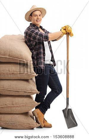 Full length portrait of an agricultural worker leaning on a pile of burlap sacks and holding a shovel isolated on white background