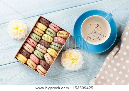 Colorful macaroons and coffee on wooden table. Sweet macarons in gift box and flowers. Top view