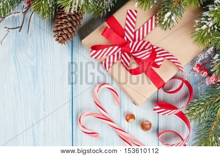 Christmas gift box and fir tree branch on wooden table. Top view with copy space