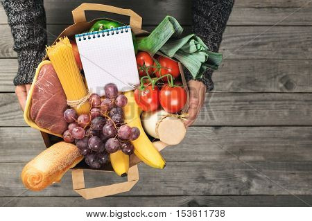 Man's hands holding paper bag of groceries with blank notebook to write your text top view with copy space