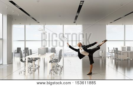 Dancing businesswoman in office room . Mixed media