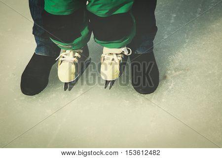 mother teaching child to skate in winter snow, kids winter sport