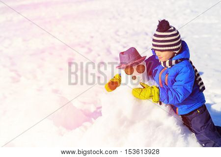 little boy with snowman in winter nature, kids winter play