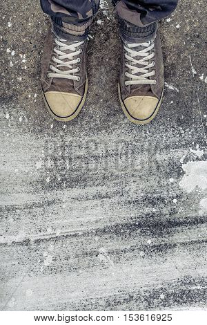 Standing on concrete floor with white drybrush stains male feet in worn sport shoes on the street