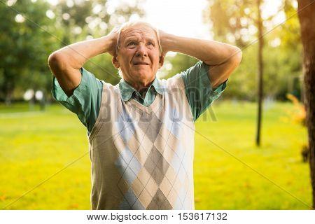 Man holding head in despair. Elderly guy outdoor. Burden of mistakes. Horrible things have happened.