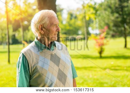 Elderly man outdoor. Old person with gray hair. Remembering the past. Find purpose of life.