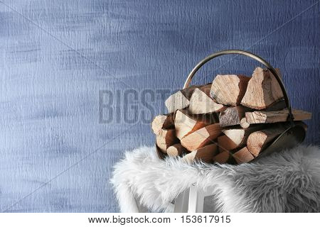 Stack of firewood on white plaid against textured wall