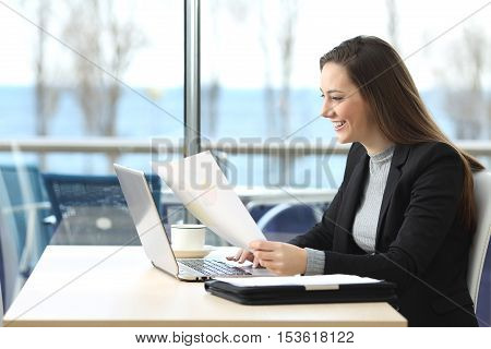 Portrait of a beautiful businesswoman working on line with a laptop and holding documents in a coffee shop with a window in the background