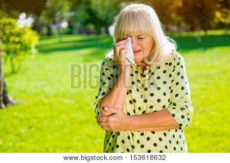 Lady wiping eye with handkerchief. Sad senior woman. I lost everything I had. Difficult period of life.