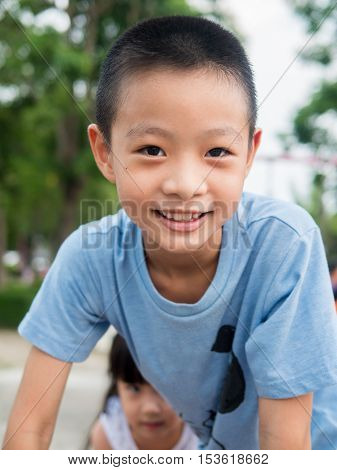 Happy asian boy playing on playground sister is behind him