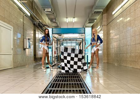 Car wash. Charming leggy girls posing with checkered flags