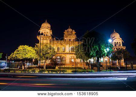 Illuminated Albert Hall Museum in Jaipur, India. Dark sky and car light trails